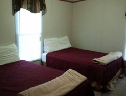 A bed or beds in a room at Oasis Lodge - Carrizo Springs