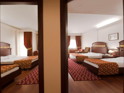 A bed or beds in a room at Botanik Hotel