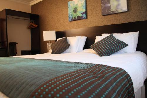 A bed or beds in a room at Greenvale Hotel