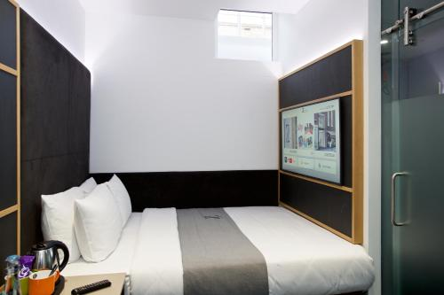 A bed or beds in a room at The Z Hotel Covent Garden