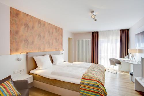 A bed or beds in a room at Elisabeth Hotel garni