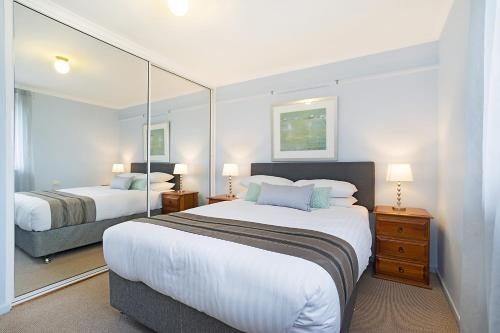 A bed or beds in a room at Newcastle Short Stay Apartments - Flagstaff Apartment