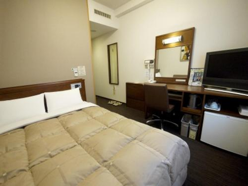 Tempat tidur dalam kamar di Hotel Route-Inn Sapporo Ekimae Kitaguchi