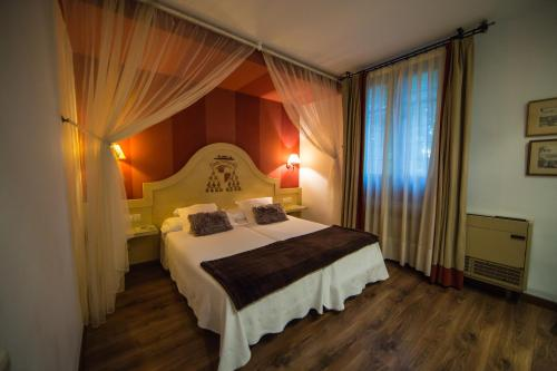 A bed or beds in a room at Hotel Hacienda del Cardenal