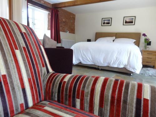 A bed or beds in a room at The Old Dairy at Bishops Barton