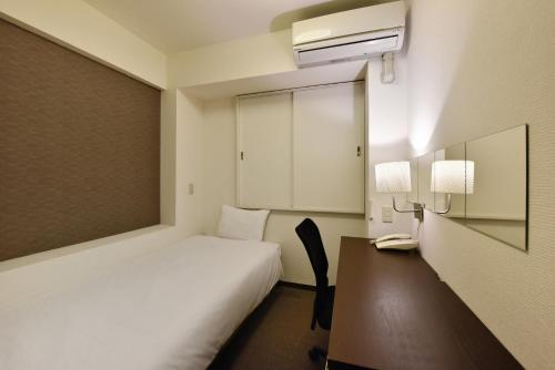 A bed or beds in a room at Hotel Kansai