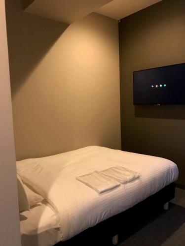 A bed or beds in a room at Kamon Hotel Seto