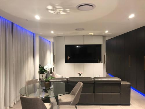 A television and/or entertainment center at Glasshouse Apartment - at Parramatta