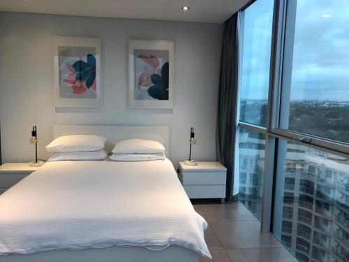 A bed or beds in a room at Glasshouse Apartment - at Parramatta