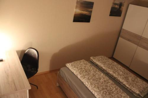 A bed or beds in a room at Pension Am Waldeck