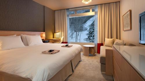A bed or beds in a room at The Green Leaf, Niseko Village