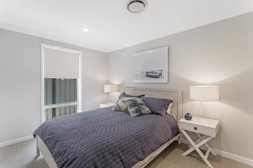 A bed or beds in a room at Wirragulla, 10 Marty Avenue - Stylish Modern House with ducted air con & WIFI