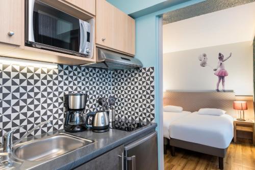 A kitchen or kitchenette at Aparthotel Adagio Paris Montmartre