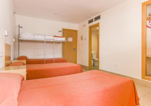 A bed or beds in a room at Albergue Inturjoven Sevilla
