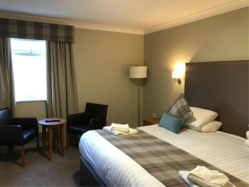 A bed or beds in a room at King Robert Hotel