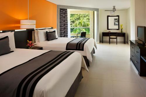 A bed or beds in a room at Dreams Huatulco Resort & Spa