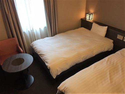 Tempat tidur dalam kamar di Dormy Inn Nagasaki Shinchichukagai