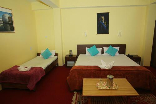 A bed or beds in a room at Rufina Hotel Swagat