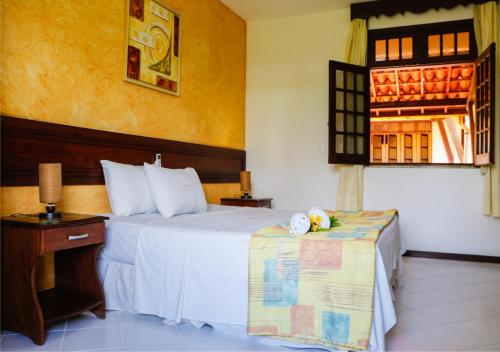 A bed or beds in a room at Girassol Praia Hotel