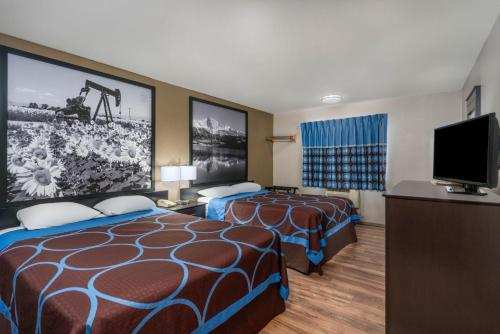 A bed or beds in a room at Super 8 by Wyndham Cortez/Mesa Verde Area