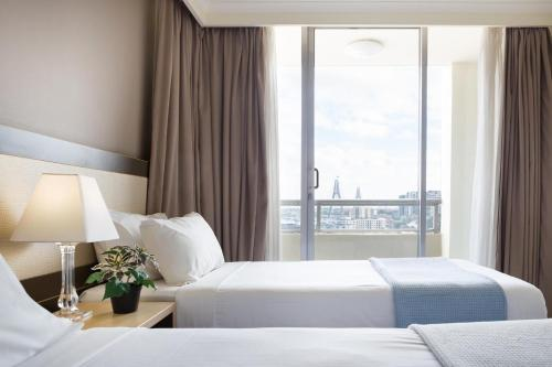 A bed or beds in a room at Resort Living And Darling Harbour At Your Door