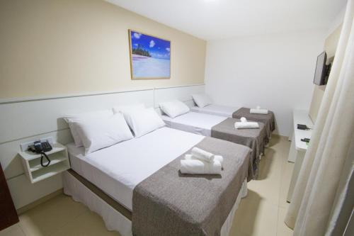 A bed or beds in a room at Pousada Kanoas