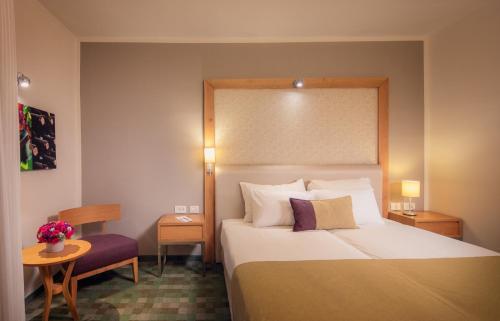 A bed or beds in a room at Prima Park Hotel Jerusalem