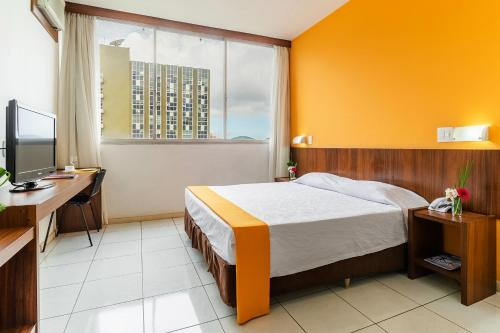 A bed or beds in a room at Alice Vitória Hotel