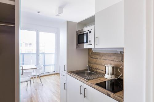 A kitchen or kitchenette at myroom - Serviced Apartments