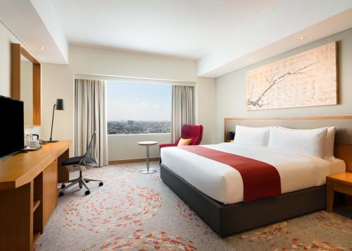 A bed or beds in a room at Holiday Inn & Suites Jakarta Gajah Mada, an IHG Hotel