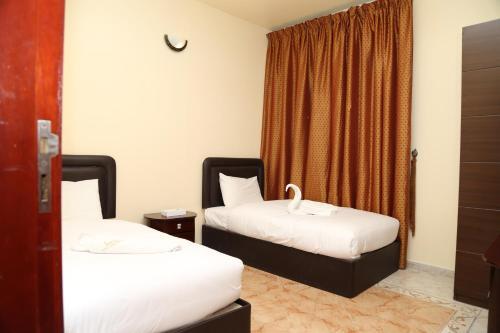 سرير أو أسرّة في غرفة في Safari Hotel Apartments - Tabasum Group