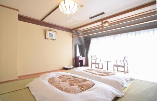 A bed or beds in a room at Nogami Honkan