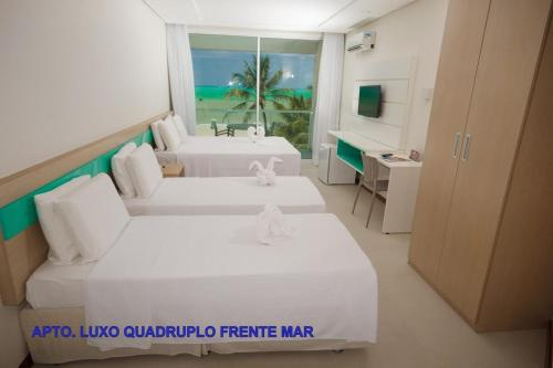 A bed or beds in a room at Hotel Praia Dourada