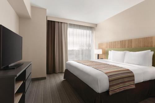 A bed or beds in a room at Country Inn & Suites by Radisson, Belleville, ON