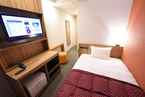 A bed or beds in a room at Hakata Green Hotel Tenjin