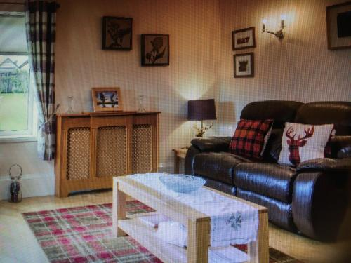 A seating area at Honeysuckle-Peaceful Scottish Cottage with Hot Tub