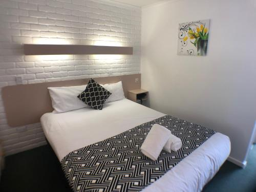 A bed or beds in a room at Jacaranda Place Motor Inn