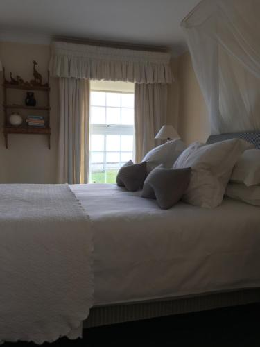 A bed or beds in a room at Romney Bay House Hotel