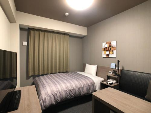 A bed or beds in a room at Hotel Route-Inn Koga Ekimae