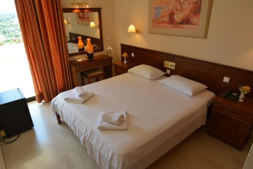 A bed or beds in a room at La Calma Hotel