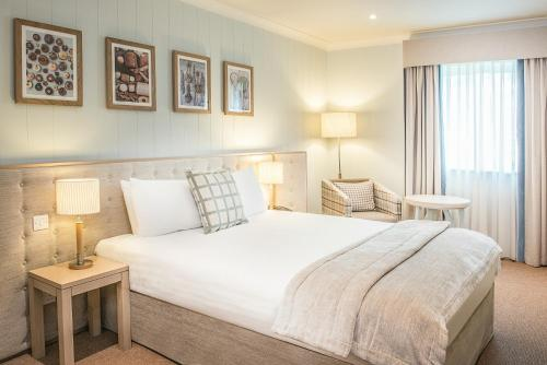 A bed or beds in a room at De Vere Cotswold Water Park