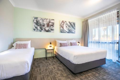 A bed or beds in a room at Nightcap at Wanneroo Tavern