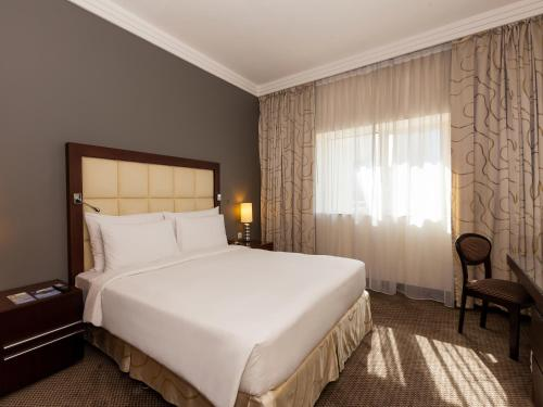 A bed or beds in a room at Deluxe Hotel Apartments