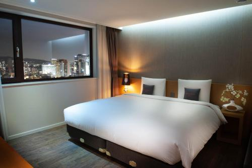 A bed or beds in a room at Amanti Hotel Seoul