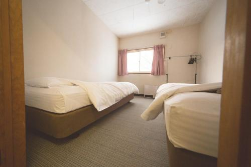 A bed or beds in a room at Hakuba Cortina Backpackers