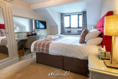 A bed or beds in a room at Wolfscastle Country Hotel