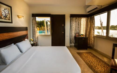 A bed or beds in a room at Obelisk Nile Hotel Aswan