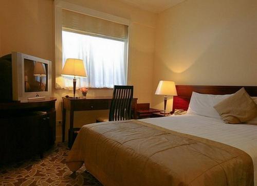 سرير أو أسرّة في غرفة في فندق أسيت شنغهاي