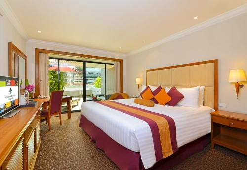 A bed or beds in a room at Boulevard Hotel Bangkok Sukhumvit