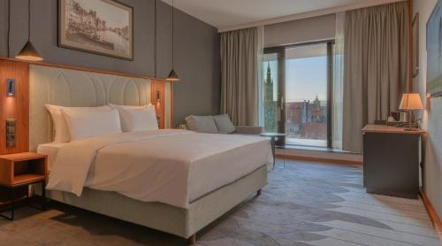 A bed or beds in a room at Radisson Hotel & Suites, Gdansk